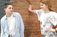 Teen Flirting. A male and female teen hangout. Boy stands relaxed against the wall while the girl leans with her hand on the wall with look of flirtation royalty free stock images
