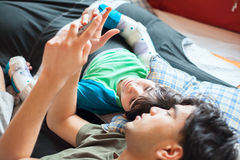Teen  on floor using computer tablet with disabled little  boy Stock Images
