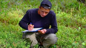 Teen with folder on the cranberries field. In forest stock video