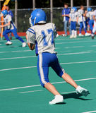 Teen Football Player Just Caught Ball. On field during game Stock Image