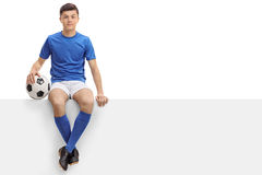 Teen football player sitting on a panel Royalty Free Stock Photo