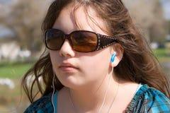 teen för musik för earbuds lyssnande allvarligt till Arkivbild