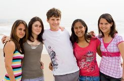 Teen friends. Happy young teen friends playing on beach Stock Image