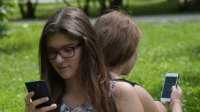 Teen friends busy with web browsing on mobile phones stock video