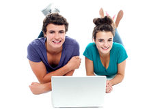 Teen friends enjoying video on laptop together. Studio shot Royalty Free Stock Image