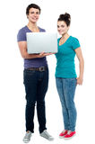 Teen friends holding laptop. Full length shot Royalty Free Stock Photography