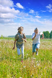 Teen  friends running at meadow Stock Images