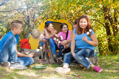 Teen friends sit on campsite with marshmallow Stock Photos