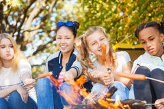 Teen friends sit on campsite with sausages Royalty Free Stock Images