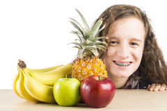 Teen with fruit. A teenage girl with a few fruit on a table isolated on white Stock Photography