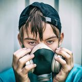 Teen in Gas Mask. Toned Photo of Teenager in the Gas Mask on the Wall Background Stock Photos
