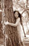 Teen girel hug a tree trunk, pine forest Royalty Free Stock Photos