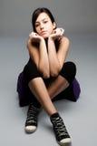 Teen girl. Brunette teen girl sitting on the floor, studio shot Stock Image