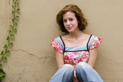 Teen Girl. PIcture of a teen girl sitting against a stucco wall that includes ivy Royalty Free Stock Images