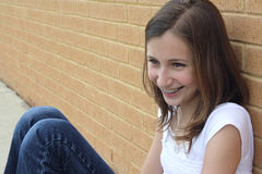 Teen girl. Smiling teen girl sits by school wall Stock Image