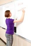 Teen Girl - Advanced Math Student. Intelligent teen girl working advanced mathematics problem on the board stock photo