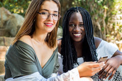 Teen girl with african friend outdoors. royalty free stock image