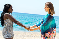 Teen girl with african girlfriend holding hands. Close up portrait of two diverse teen girls holding hands on beach stock images