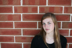 Teen girl against brick wall Royalty Free Stock Photos