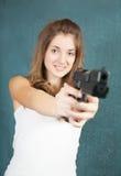 Teen girl aiming a gun. Long-haired teen girl aiming a black gun Royalty Free Stock Photo