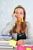 Teen girl with al lot to remember. Teen girl sitting at desk with homework for school and having a lot to remember Royalty Free Stock Photos