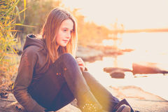 Teen girl alone. Thoughtful teen girl in casual cloth alone looking to water at sunset Stock Photo
