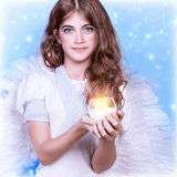 Teen girl angel. Closeup portrait of cute teen girl wearing angel costume on blue winter background, Christmas holidays, religion concept Royalty Free Stock Images