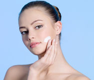 Teen girl applying cream on cheek Stock Images