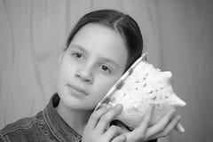 Teen girl applying a seashell to his ear listening Stock Photos