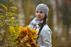 Teen girl in the autumn park with maple leaves Stock Photos