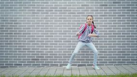 Teen girl back to school. Teen girl with backpack go to school moves on street next to an Brick Wall. Cute child with bag showing different emotions Back to stock video