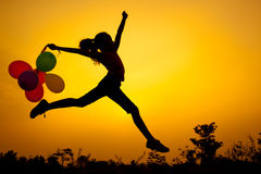Teen girl with balloons jumping on the nature. Of the evening Royalty Free Stock Photography
