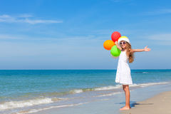 Teen girl with balloons standing on the beach Royalty Free Stock Photos