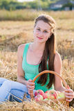 Teen girl with a basket of apples in  field Stock Image