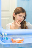 Teen girl in bathroom. Using cosmetic cream Royalty Free Stock Photography