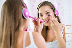 Teen girl in bathroom. Makeup and listening to music Stock Photo