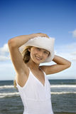 Teen Girl at the Beach. Teen girl holds her hat down on her head while at the beach. Vertical shot Royalty Free Stock Photos