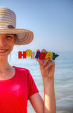 Teen girl at a beach. Holding word 'Holiday Royalty Free Stock Photos