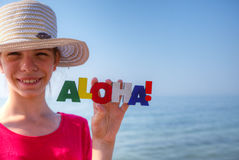 Teen girl at a beach. Holding word 'Aloha Stock Images