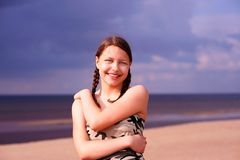 Teen girl on a beach. Cute happy teen gir staying on a beach and smiling Royalty Free Stock Images