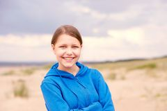 Teen girl on a beach. Cute happy teen girl staying on a beach and smiling Royalty Free Stock Images