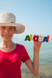 Teen girl at a beach. Holding word 'Aloha Royalty Free Stock Image