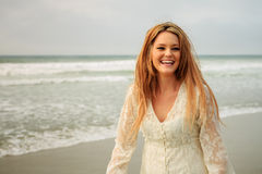 Teen girl at the beach laughing. Sexy teen girl in white lace dress Stock Image