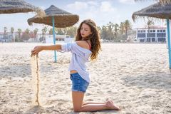 Teen girl on the beach playing with sand. Near thatch umbrellas Royalty Free Stock Photography