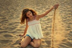 Teen girl on the beach playing with sand. In the wind Royalty Free Stock Photography