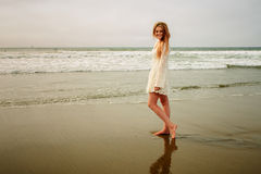 Teen girl at the beach in wet sand. Sexy teen girl in white lace dress Royalty Free Stock Photo