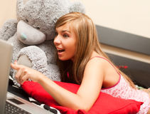 Teen girl in bed with laptop. Young teen blond woman in bed in chaos of clothes with laptop Stock Images