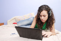 Teen girl in bed looking on her laptop Royalty Free Stock Photography