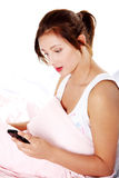 Teen girl in bed reading sms. Royalty Free Stock Images