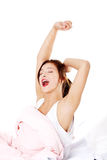 Teen girl in bed yawning. Stock Photo